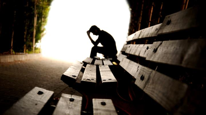 Silhouette of person with head in hands on park bench